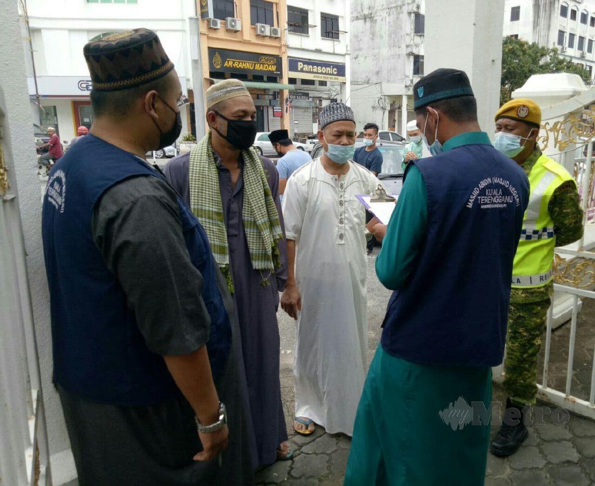 JAWATANKUASA masjid Abidin sedang menyemak senarai ama jemaah undangan dipintu masuk. FOTO Baharom Bakar
