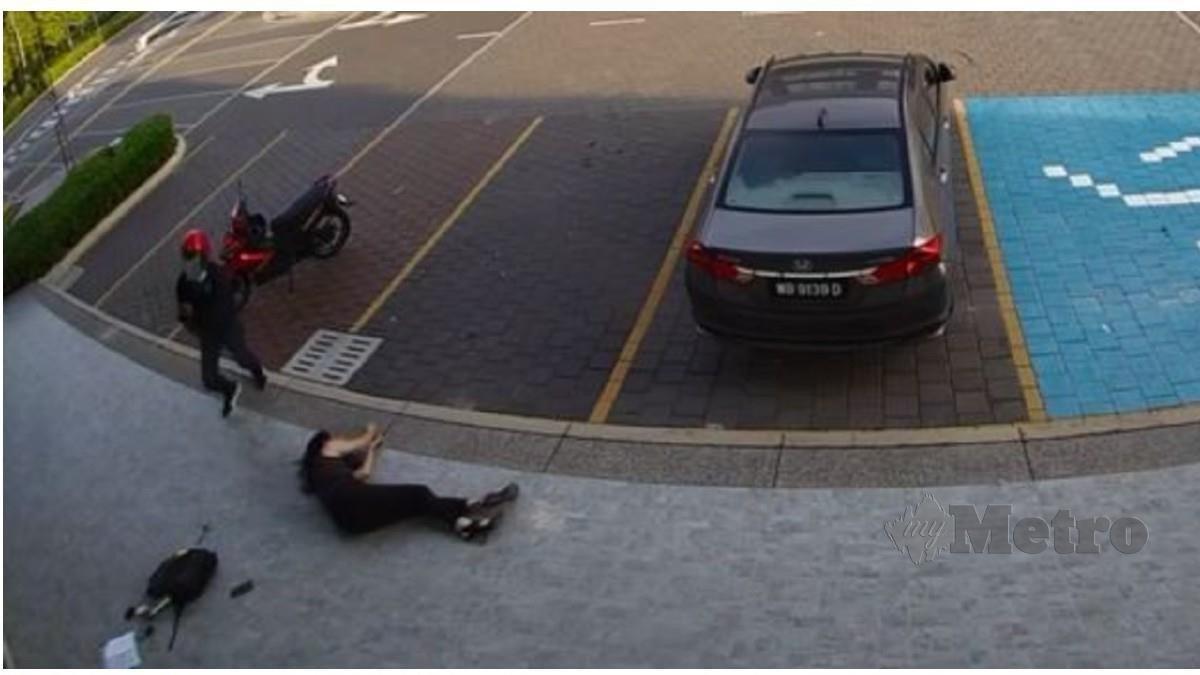 MANGSA terjatuh selepas diragut lelaki bermotosikal bersenjatakan parang, hari ini. FOTO ihsan pembaca.